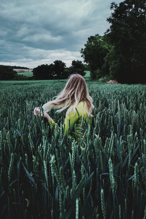 Young woman in field of green plants