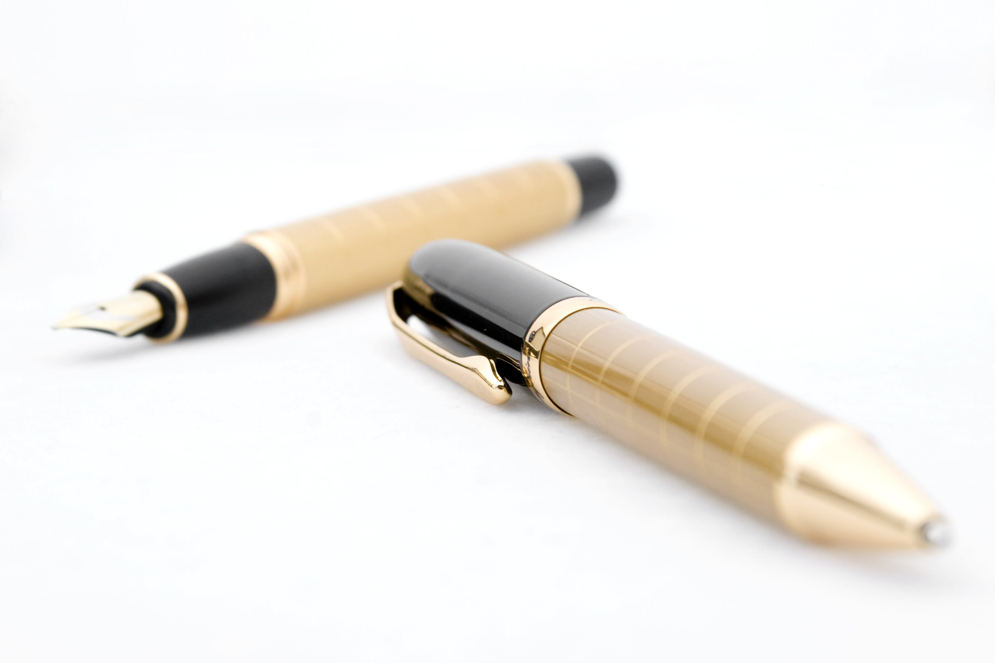 Two Brown-and-black Pen and Fountain Pen on White Background