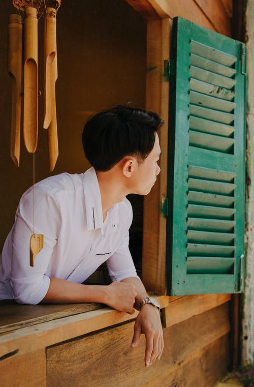 Side view of dreamy ethnic male in stylish apparel looking out of window of wooden house near decorative wind bell