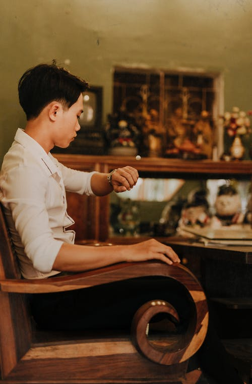 Side view of young stylish ethnic male checking time while sitting in decorative wooden chair in house