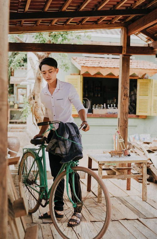 Young wistful Asian guy in trendy clothes with bike looking down on roofed terrace near road