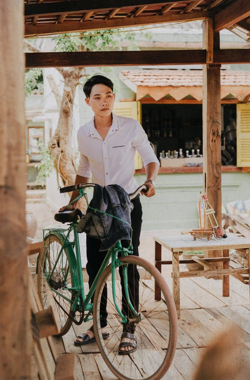 Melancholic Asian guy with bike on roofed terrace