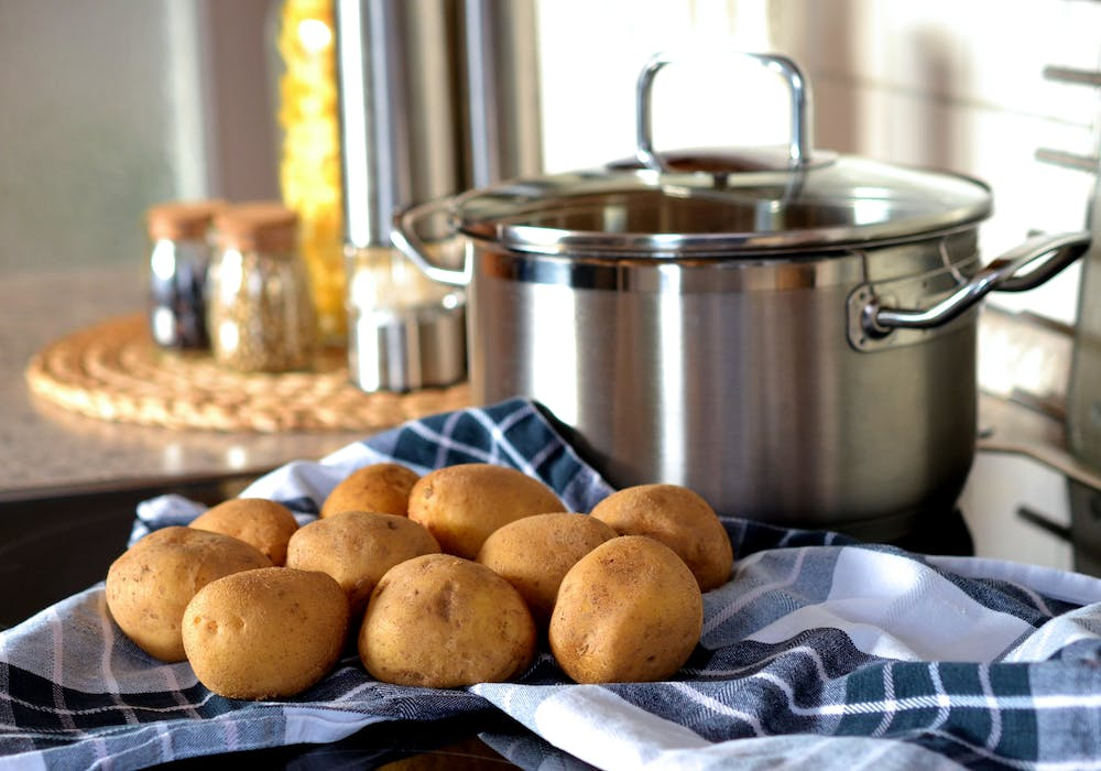 Potatoes next to a stainless steel cooking pot.. | Photo: Pexels