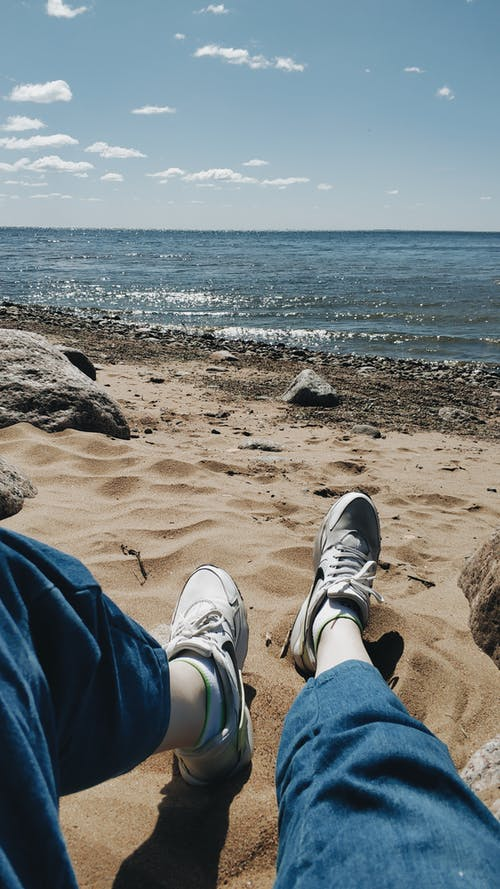 Person in Blue Jeans and White Sneakers on the Beach