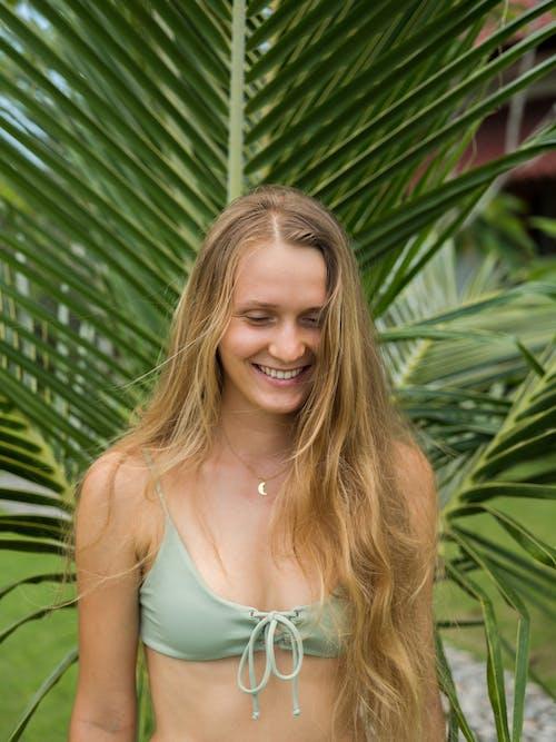 Happy young woman in bikini standing in garden