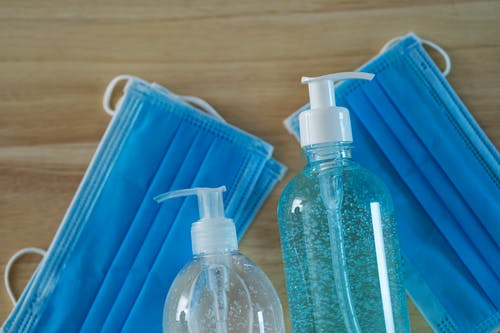 Liquid soap and gel dispensers with medical masks on table