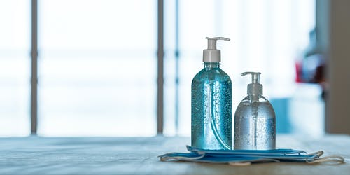 Set of dispensers with liquid soap and gel near masks