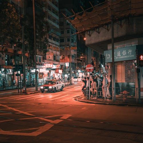 Unrecognizable pedestrians and aged car near crosswalk in night city