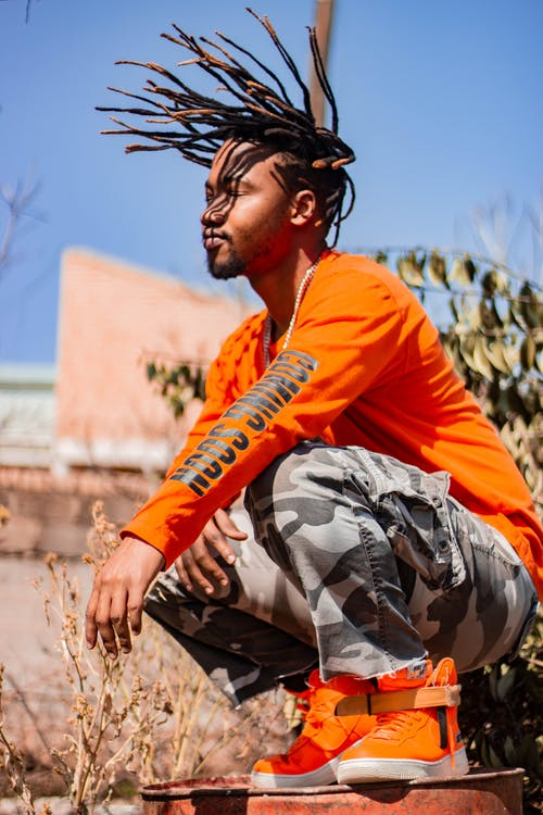 From below side view of trendy African American male with creative hairstyle in bright footwear squatting with closed eyes under blue sky