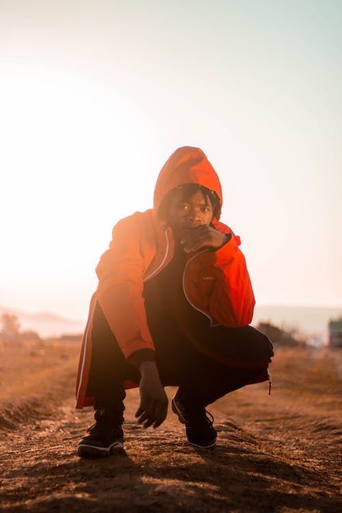 Ground level of stylish African American guy in hood touching face while squatting on dry terrain and looking away under sky at sundown