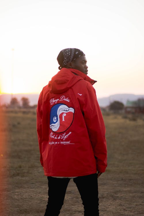 Back view of contemplative black male in red jacket with ornament standing on green meadow while looking away