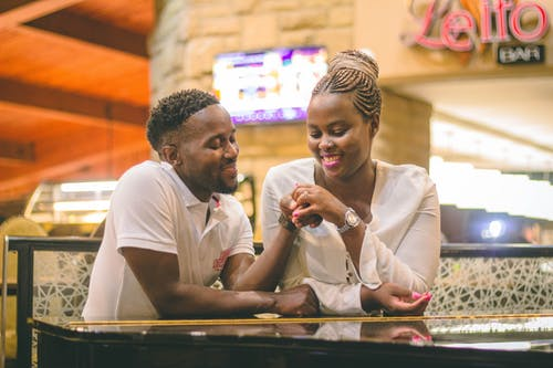Cheerful African American couple with creative hairstyles sitting in cafe