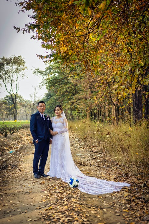 Woman in White Wedding Gown Beside Man in Black Suit