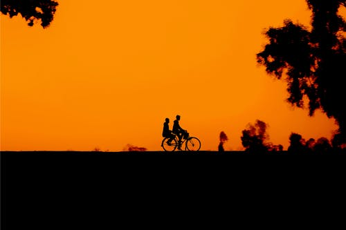 Unrecognizable people riding bicycle against sunset