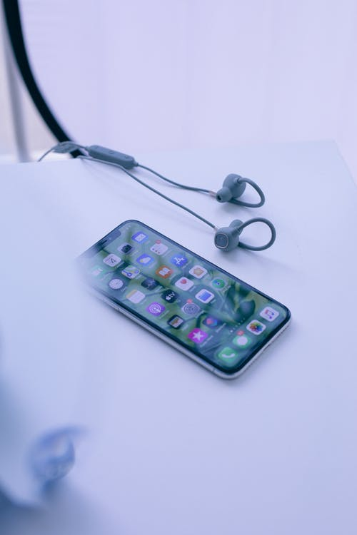 Modern smartphone on table near earphones