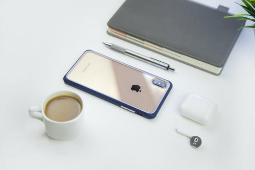 Smartphone with cup of coffee and earbud on table