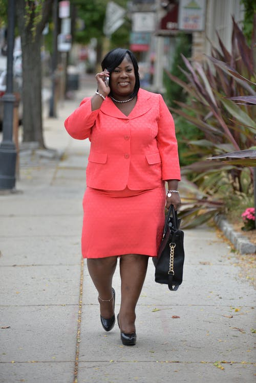 Trendy cheerful African American female in colorful apparel with handbag talking on cellphone while walking on street