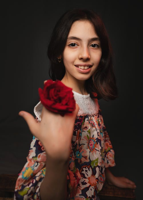 Woman in White Green and Red Floral Dress Holding Red Rose