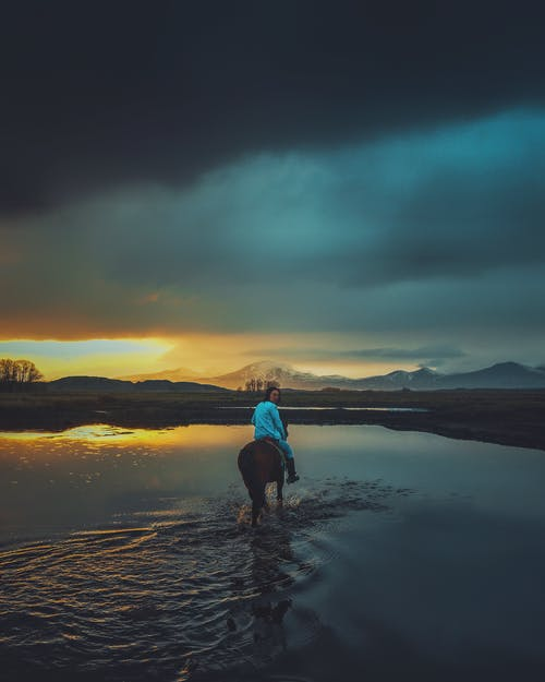 Anonymous person riding horse in lake near mountains at sunset