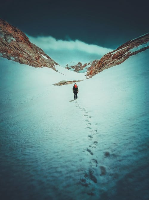 Back view of unrecognizable hiker in warm clothes walking on snowy mountain slope against blue sky