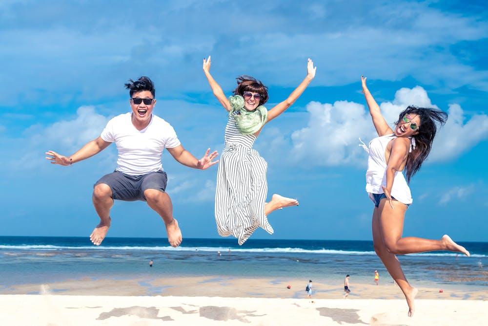 Man and women jumping on seashore.    Photo: Pexels