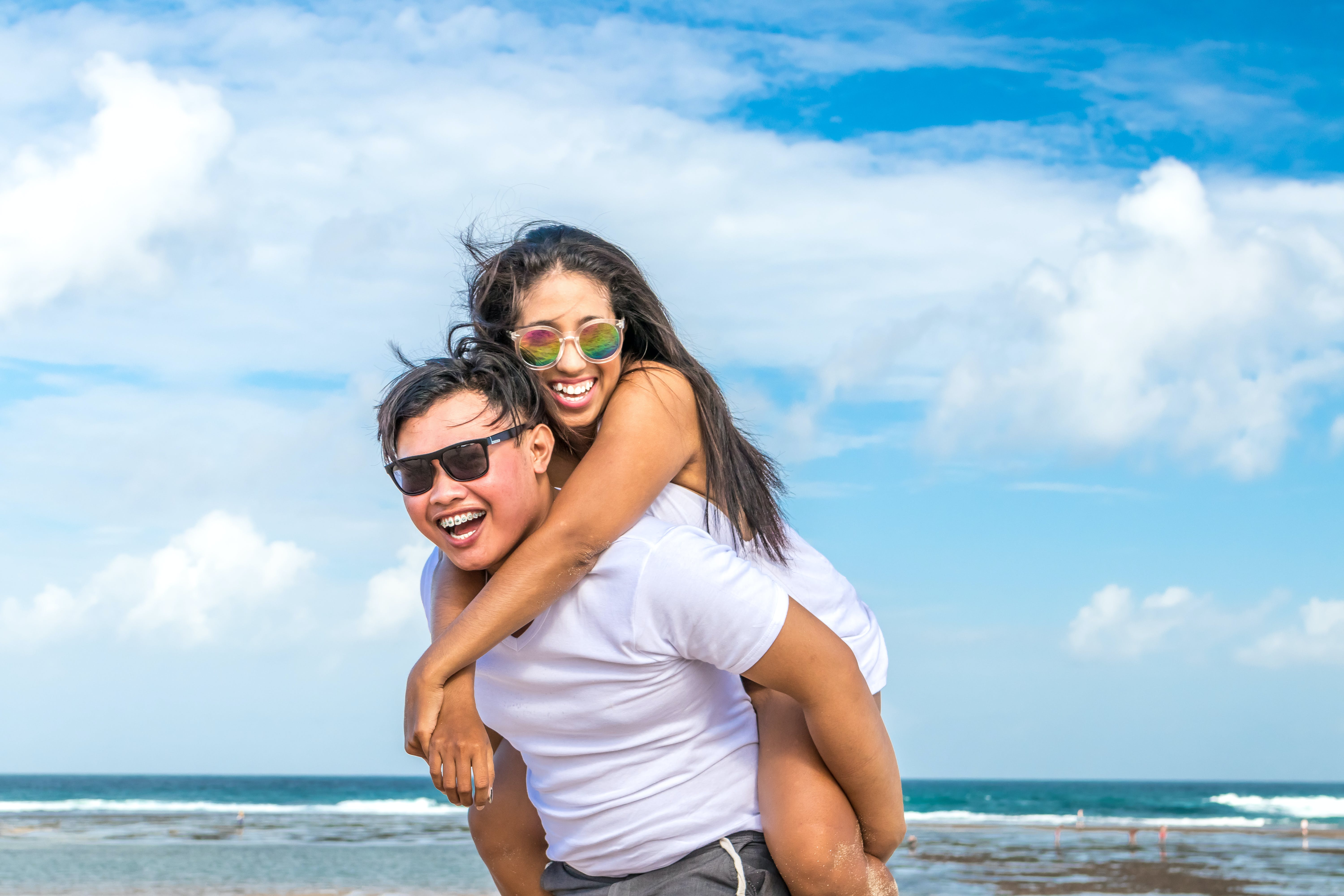 Man Carrying Woman on Back Smiling