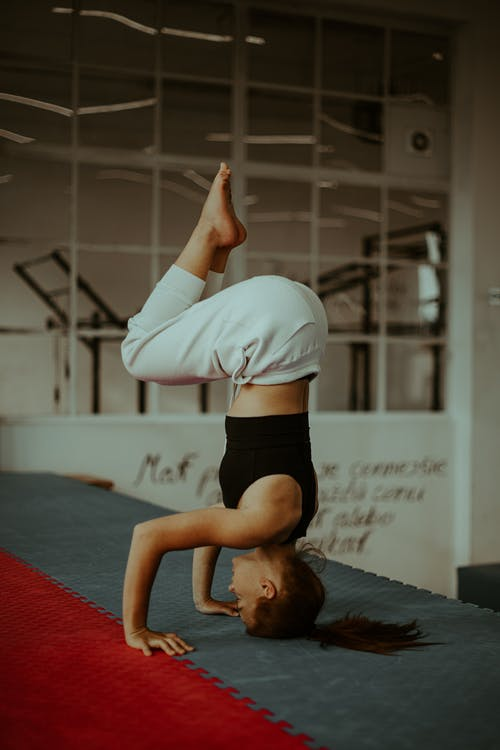 Determined young woman standing on head during yoga training