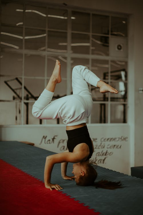Concentrated young female performing Salamba Sirsasana headstand exercise during yoga training