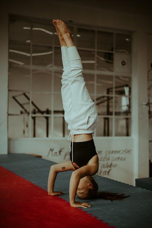 Active young woman doing Tripod Headstand asana during yoga training