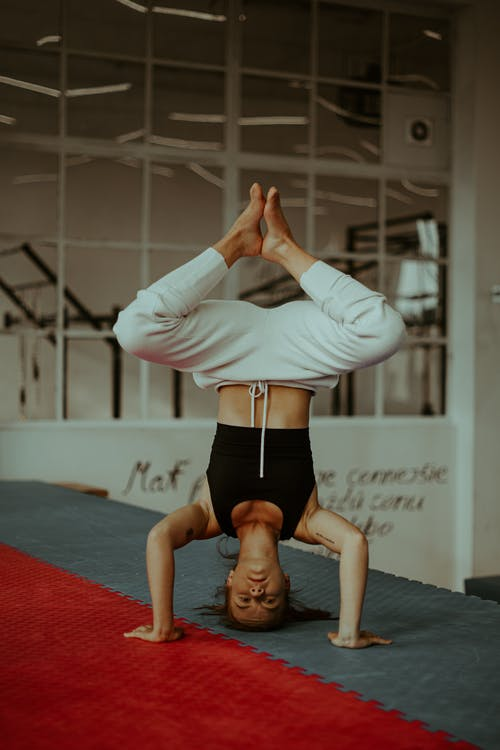 Serious young barefooted woman showing Bound Angle Headstand yoga asana