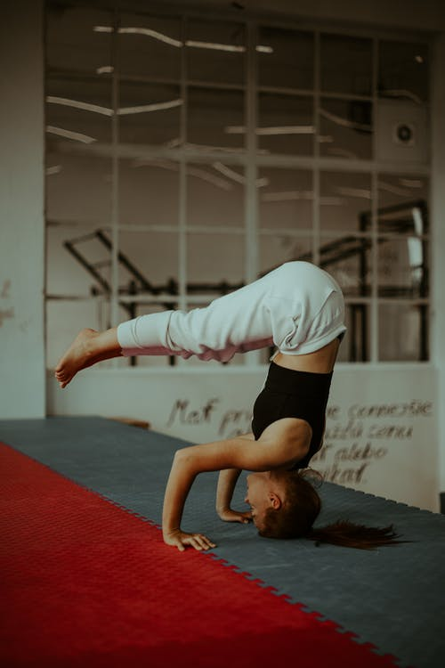 Slender female practicing Supported Headstand with Legs Halfway Down yoga asana