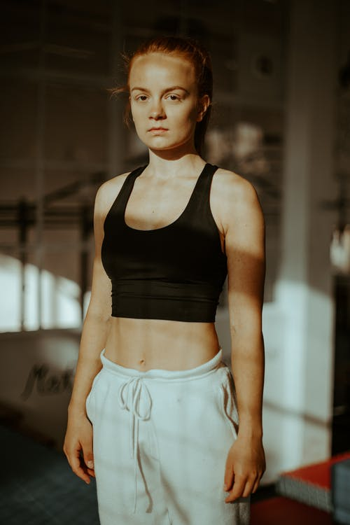 Exhausted young female athlete relaxing in sports center