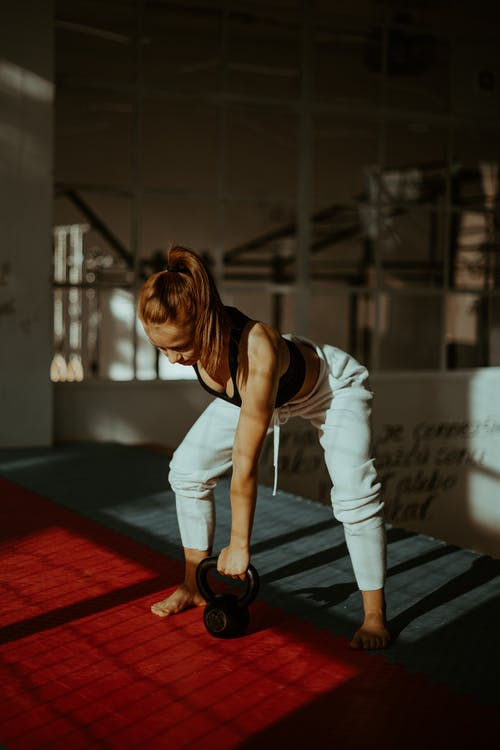 Young muscular female doing kettlebell arm exercise in sports club