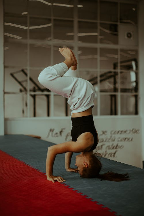 Focused young woman doing Salamba Sirsasana Baddha Konasana headstand yoga pose