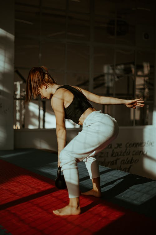 Muscular young lady during fitness training with kettlebell in gym