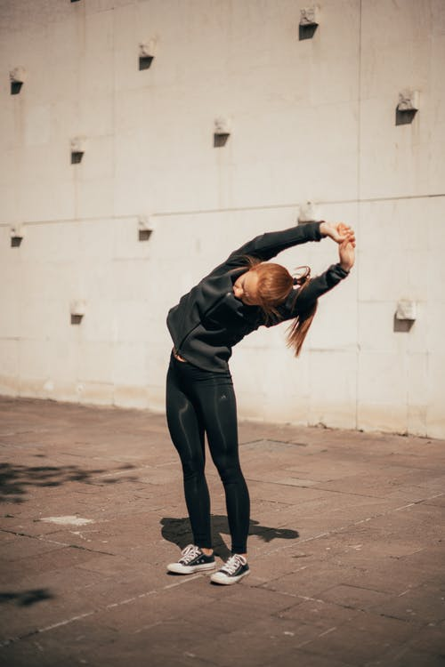 Active young woman stretching body on street before training on sunny day