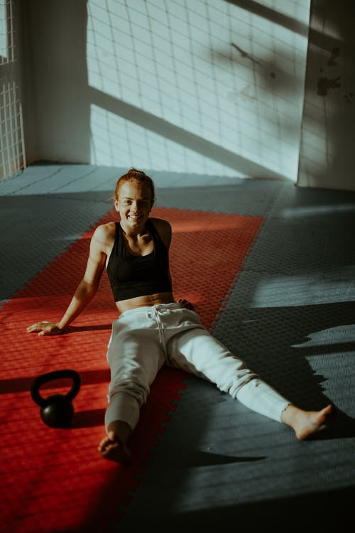Positive young sportswoman recreating on mat after workout