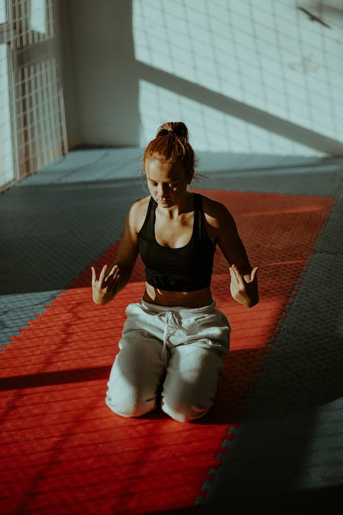 Focused young woman meditating in fitness center