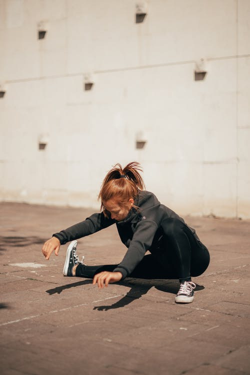 Young sportswoman stretching legs before workout on street
