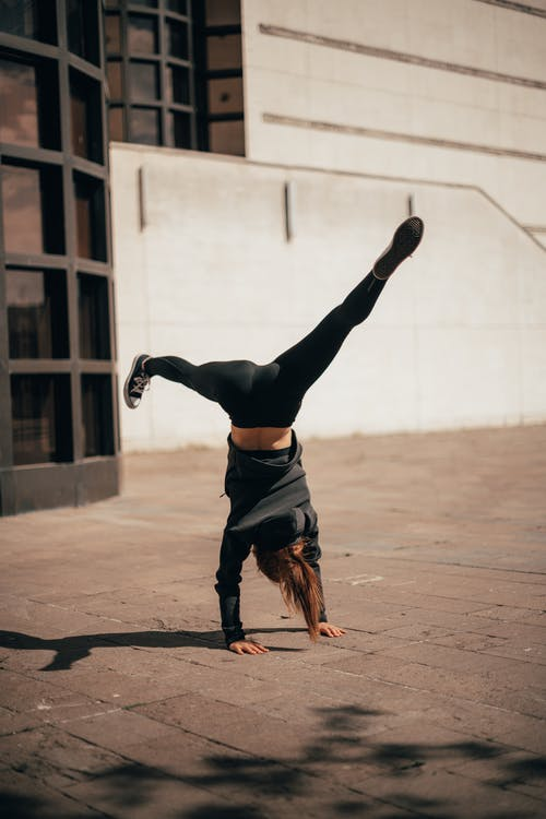 Slim young lady showing Handstand with Splits during yoga training on street