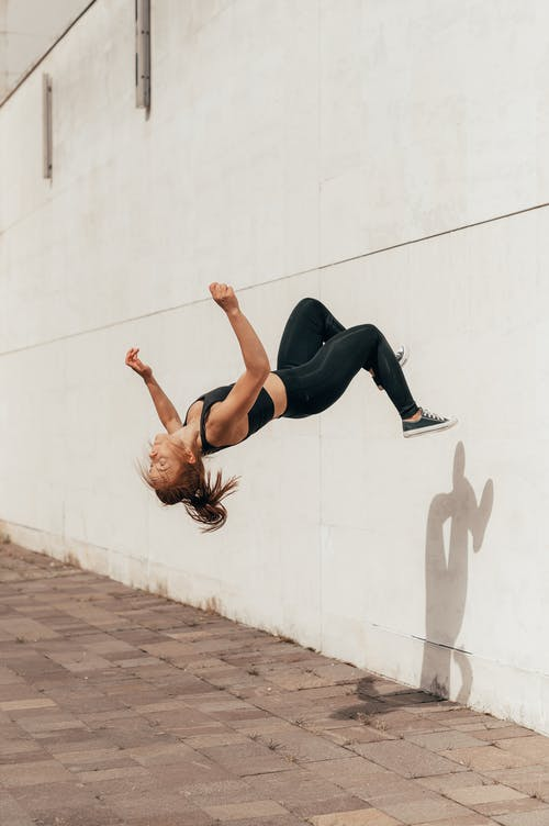 Fit active young sportswoman practicing backflip off wall on street