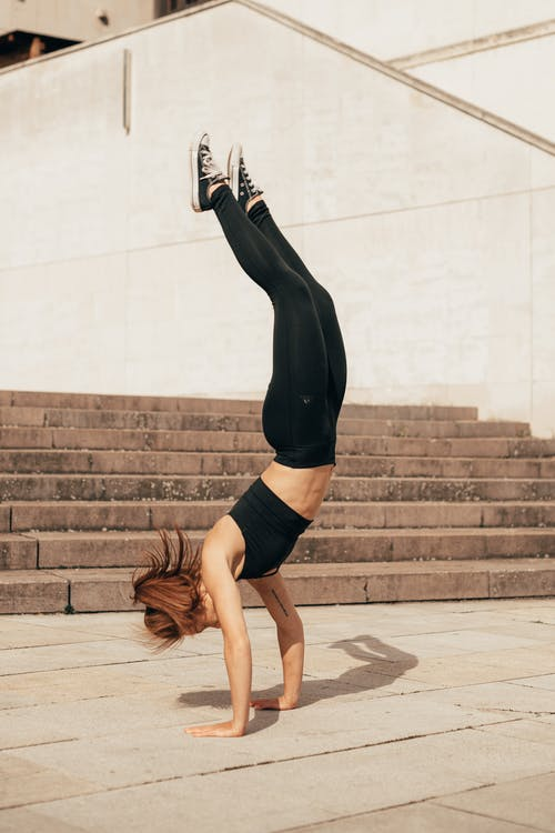 Determined young active lady standing on hands during outdoor workout