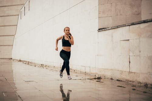 Strong young runner jogging on wet ground during outdoor training