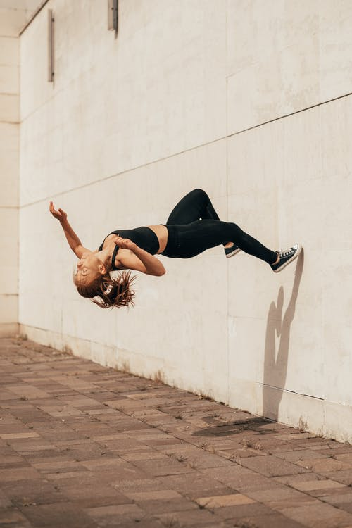 Young sportswoman jumping somersault off wall on street