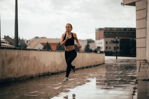 Active young woman running along street near buildings on rainy day