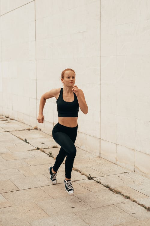 Young sportswoman sprinting against concrete wall
