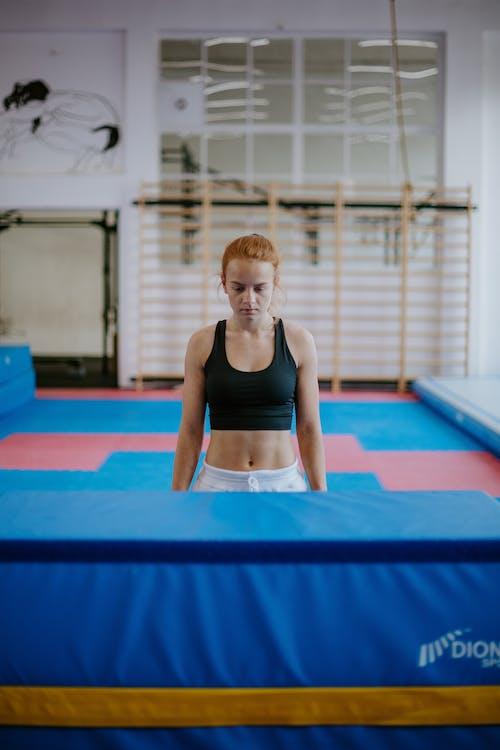 Sportswoman practicing gymnastics on mat