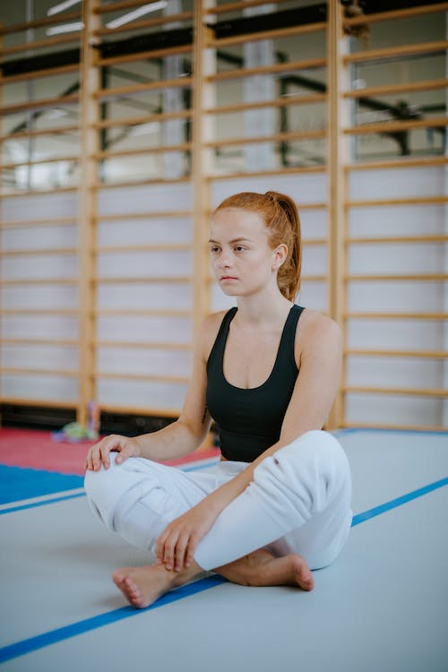 Woman resting in gym with legs crossed