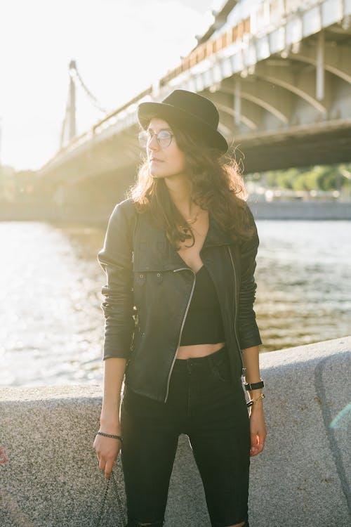 Stylish woman in eyeglasses standing near river