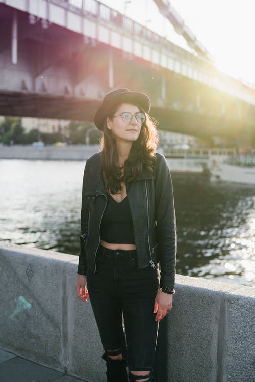 Positive stylish woman standing on river embankment looking away